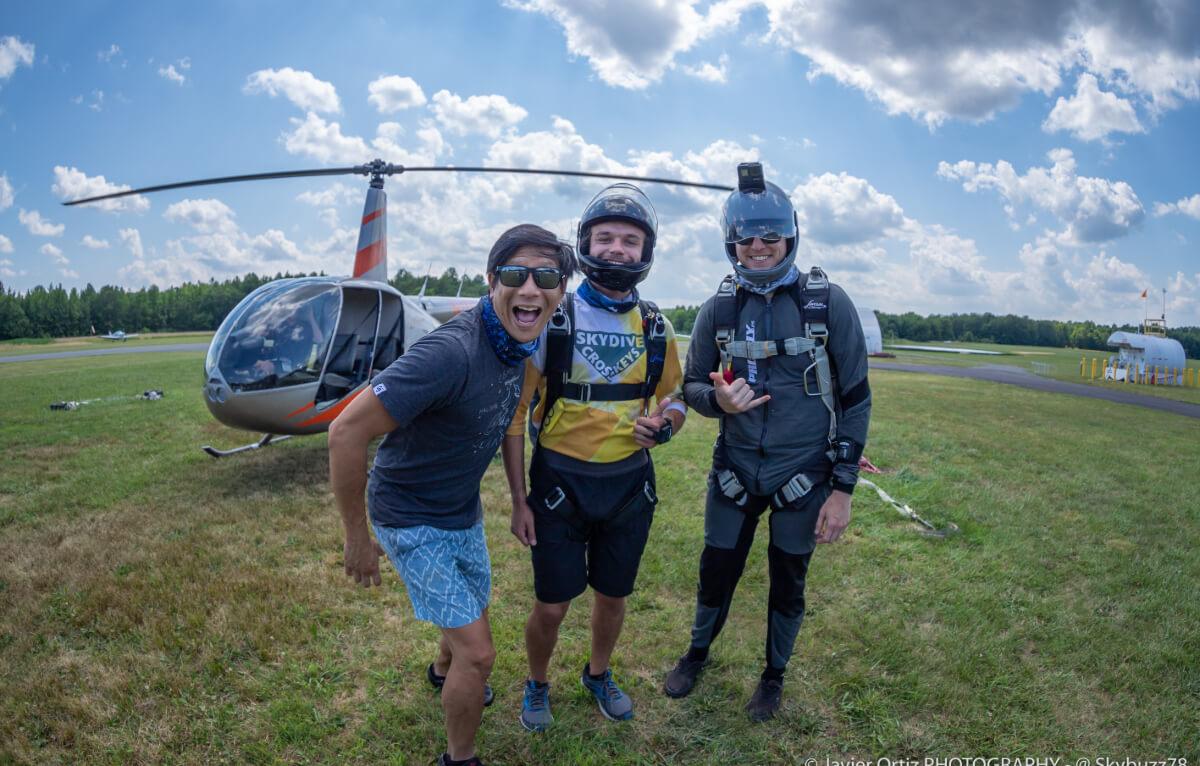 Three skydivers smile at the camera.