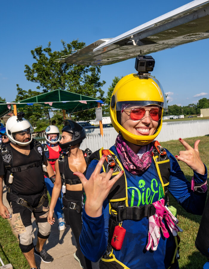 Skydiver sticks her tongue out while boarding the plane.