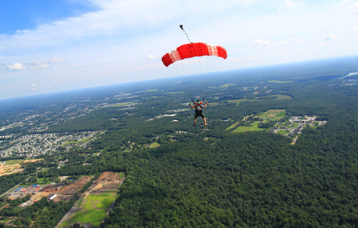 skydiver glides with parachute over forest.