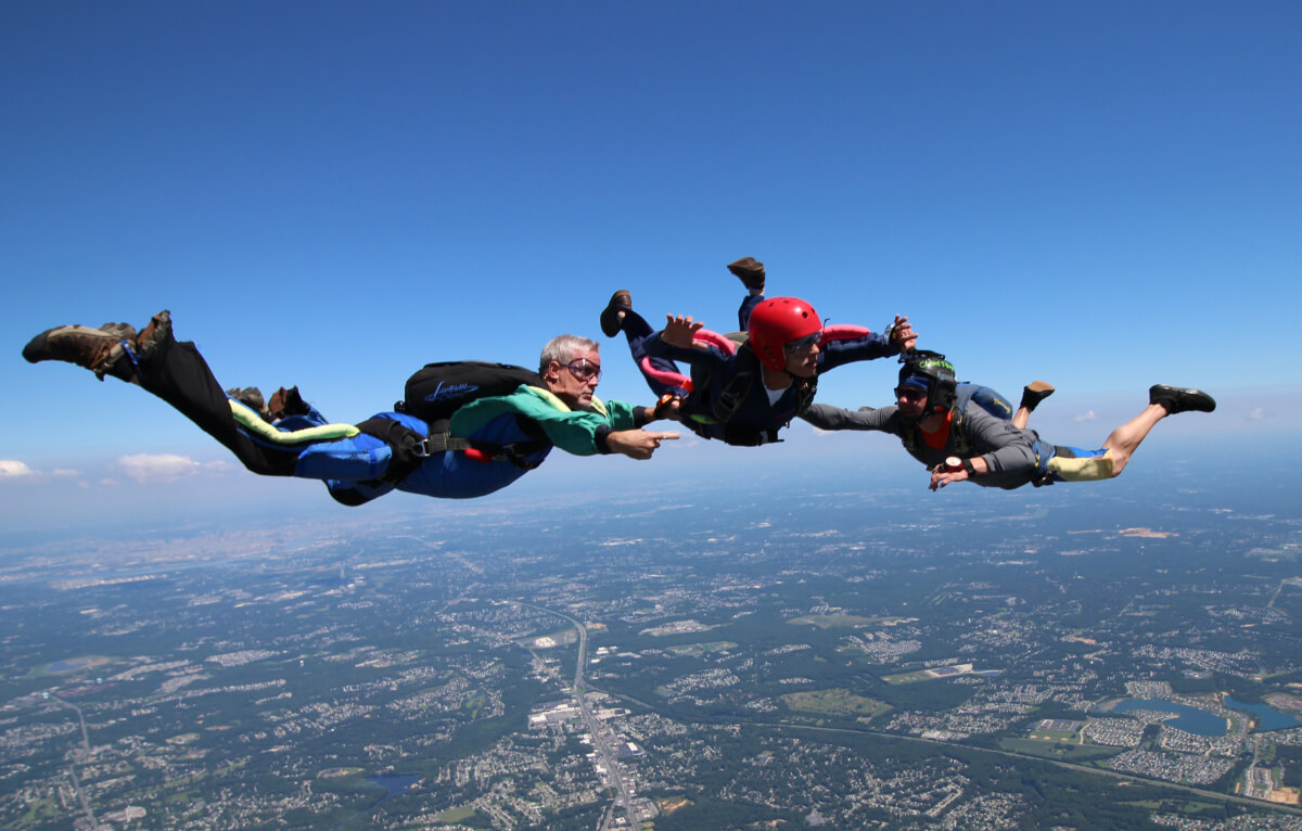 Three skydivers float in the air.