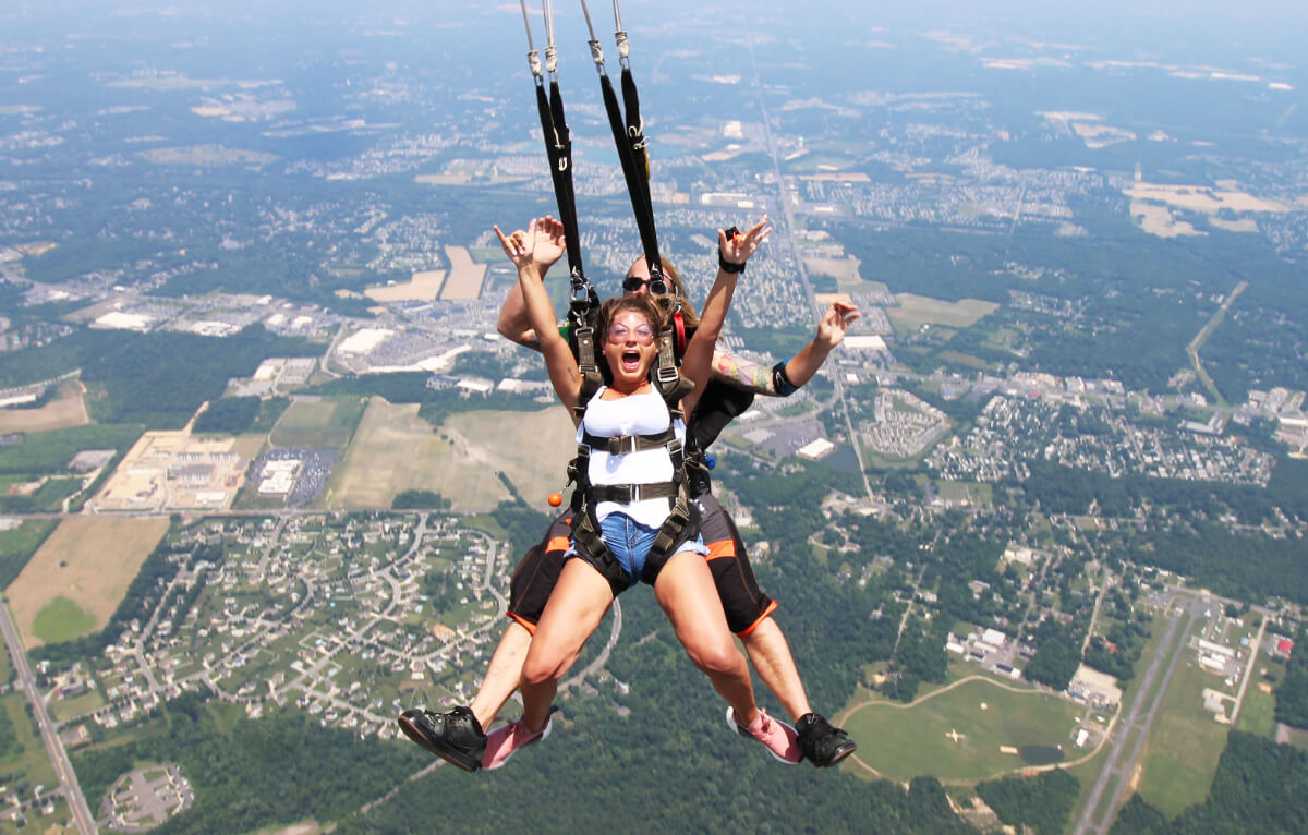 Girl raises arms as she glides on tandem parachute ride.